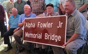 Citizens holding the new sign for the Alpha Fowler Jr Memorial Bridge.